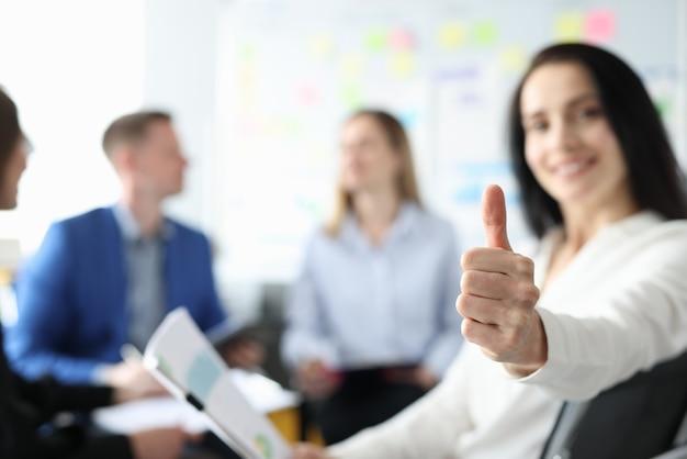 Mulher de negócios sorridente levanta o polegar atrás de sua equipe de empresários