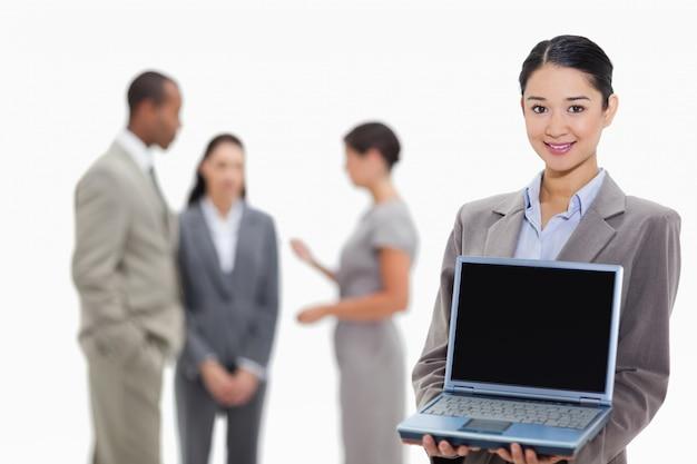 Mulher de negócios sorridente mostrando uma tela de laptop com colegas de trabalho no fundo