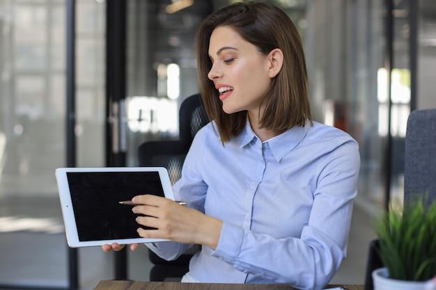 Mulher de negócios sorridente, olhando para a câmera, fazer uma conferência ou chamada de negócios, gravando um videoblog, conversando com o cliente.