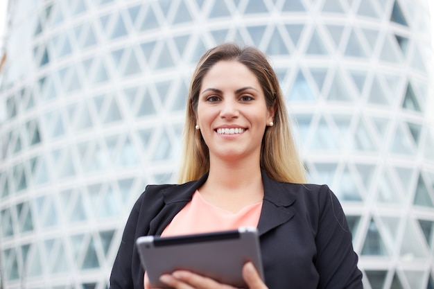 Mulher de negócios sorridente segurando um tablet digital em ambiente urbano
