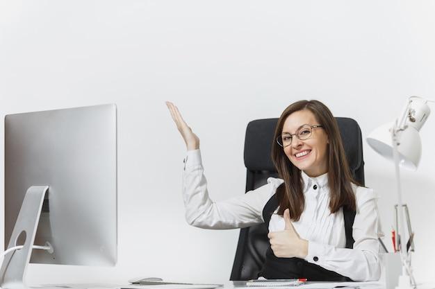 Mulher de negócios sorridente, sentada à mesa, trabalhando no computador com documentos em um escritório leve