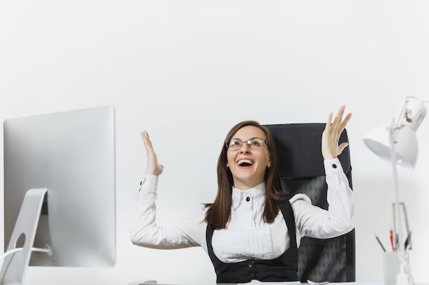 Mulher de negócios sorridente, sentada à mesa, trabalhando no computador com um monitor moderno e documentos no escritório, regozijando-se com o sucesso, segurando as mãos, copie o espaço para propaganda Foto gratuita