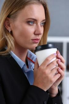 Mulher de negócios sorridente tomando café de um papel