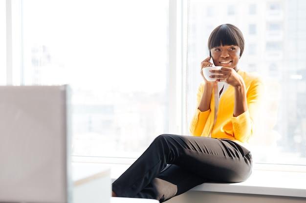 Mulher de negócios sorridente tomando café e falando ao telefone no escritório