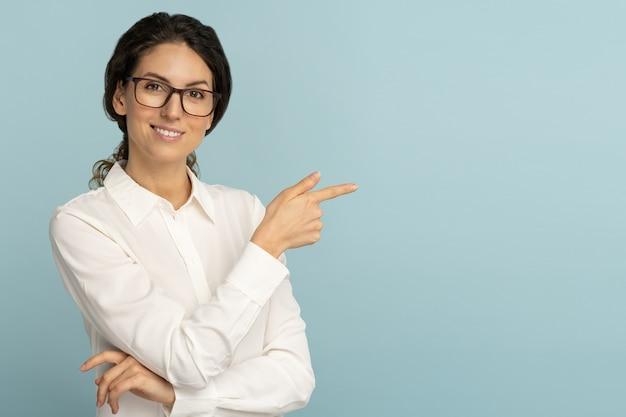 Mulher de negócios sorridente usa blusa branca e óculos apontando com o dedo, mostrando o espaço em branco da cópia para publicidade, oferta, produto, promoção, venda, isolado no fundo azul do estúdio