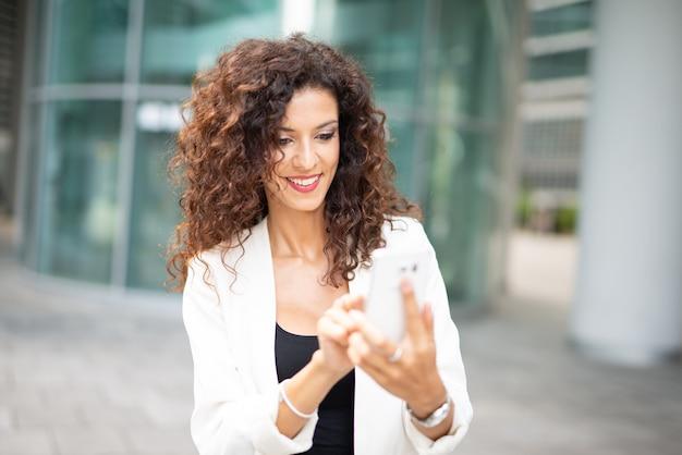 Mulher de negócios sorridente usando seu telefone celular enquanto caminhava ao ar livre