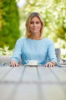 Mulher de negócios, sorrindo com café em uma mesa no terraço de verão
