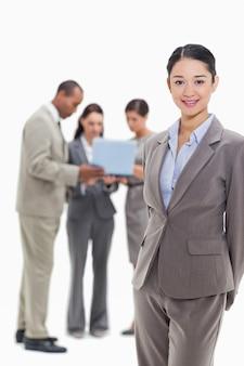 Mulher de negócios sorrindo com colegas de trabalho assistindo um laptop no fundo