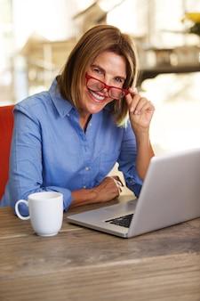 Mulher de negócios sorrindo na mesa e trabalhando com o computador portátil