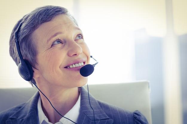 Mulher de negócios sorrindo telefonando com fone de ouvido