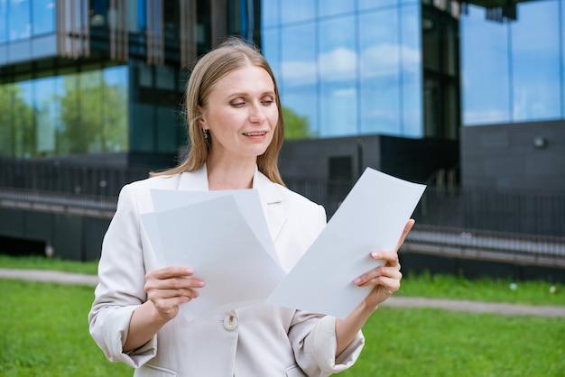 Mulher de negócios suburbana bonita andando em edifícios de escritórios urbanos clássicos segurando papel docu ... Foto Premium