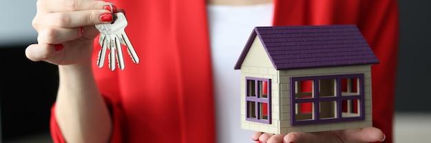 Mulher de negócios tem as chaves e uma pequena casa nas mãos.