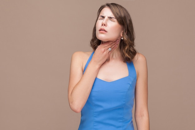 Mulher de negócios tem dor no pescoço. foto de estúdio, fundo marrom claro