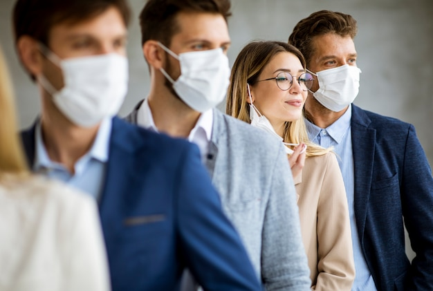 Mulher de negócios tirando a máscara facial protetora e olhando para a câmera com os membros da equipe em pé na fila do escritório