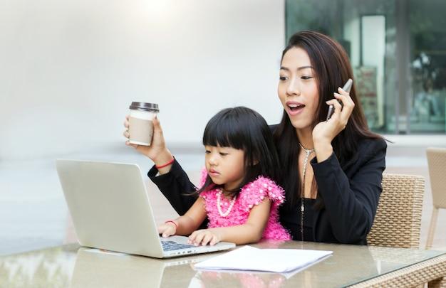 Mulher de negócios trabalha em casa com sua filha