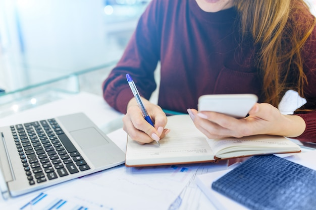 Mulher de negócios trabalha em casa, trabalho remoto em casa, com laptop e notebook, faz anotações no telefone