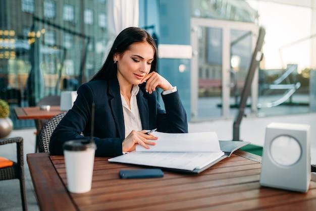 Mulher de negócios trabalha na hora do almoço no café. edifício moderno, centro financeiro, paisagem urbana. mulher de negócios de terno no local de trabalho