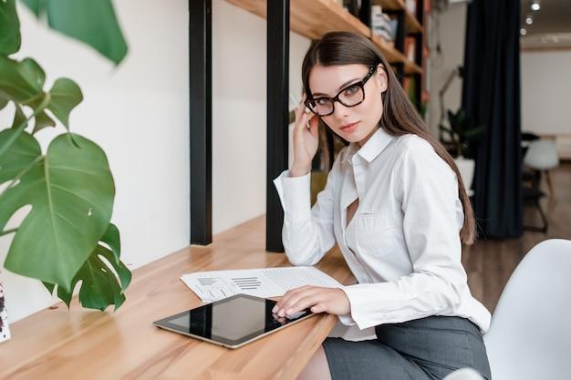 Mulher de negócios trabalha no escritório com tablet e documentos com gráficos