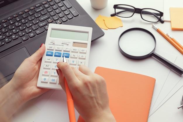 Mulher de negócios, trabalhando com dados financeiros mão usando calculadora