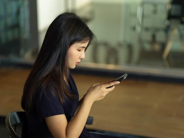 Mulher de negócios trabalhando com smartphone enquanto está sentada na divisória de vidro da sala de escritório