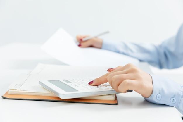 Mulher de negócios, trabalhando com uma calculadora com um fundo branco