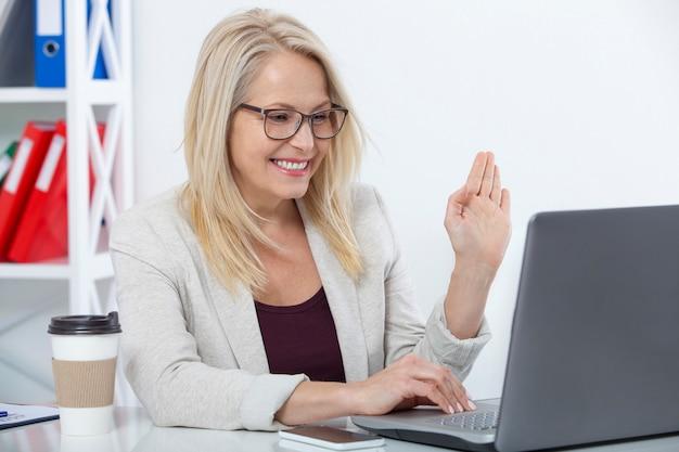 Mulher de negócios trabalhando, conversando com o laptop no escritório, em casa. trabalhe em casa conceito