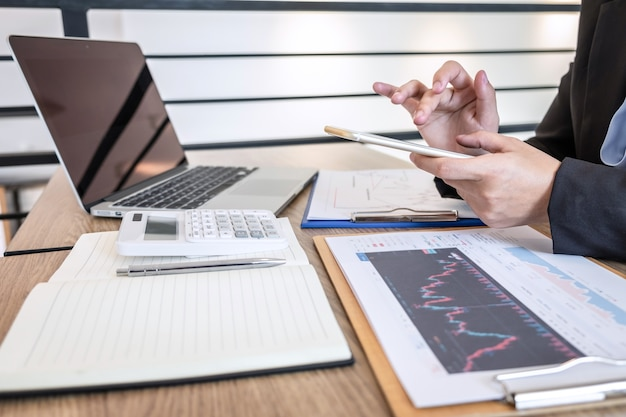 Mulher de negócios trabalhando e planejando em projeto de marketing de negociação de investimento e usando a calculadora para analisar o gráfico de dados do negócio de uma bolsa de valores para o lucro financeiro do negócio.