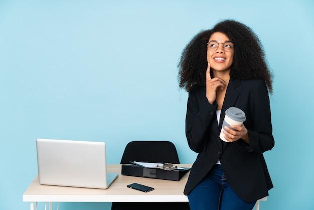 Mulher de negócios, trabalhando em seu local de trabalho, pensando em uma idéia enquanto olha para cima