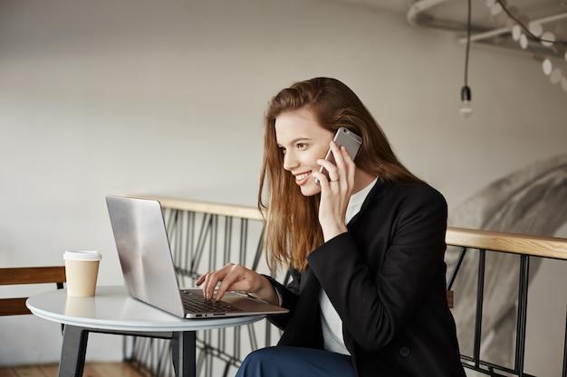 Mulher de negócios trabalhando em um café, falando no telefone e olhando para o laptop