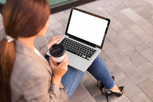 Mulher de negócios trabalhando em um laptop ao ar livre enquanto toma um café