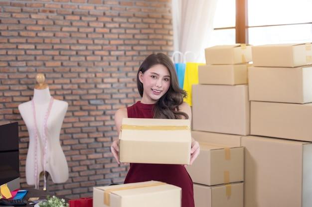 Mulher de negócios trabalhando em uma pme em casa com internet online enviando um pacote