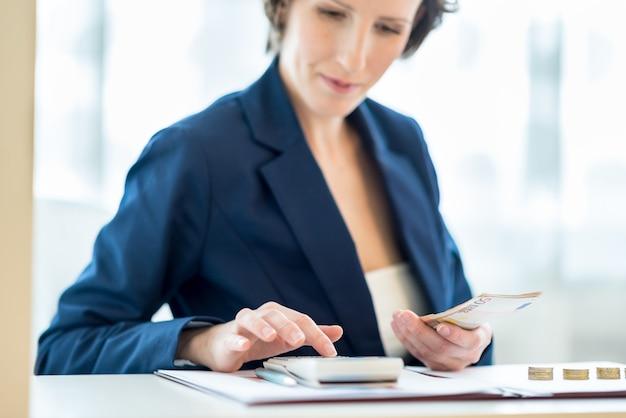 Mulher de negócios trabalhando na calculadora com moedas de ouro em sua mesa branca. concentre-se na mão dela e nas notas de euro.