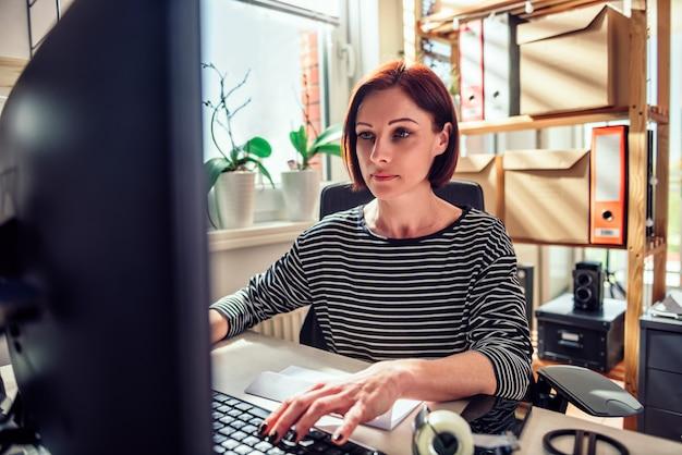 Mulher de negócios, trabalhando no computador no escritório