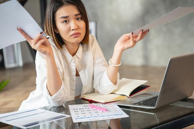 Mulher de negócios triste com projeto olhando para a câmera no escritório