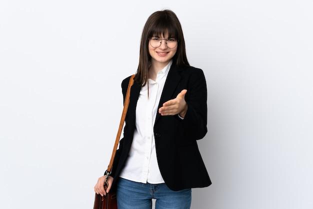 Mulher de negócios ucraniana isolada em uma parede branca, apertando a mão após um bom negócio