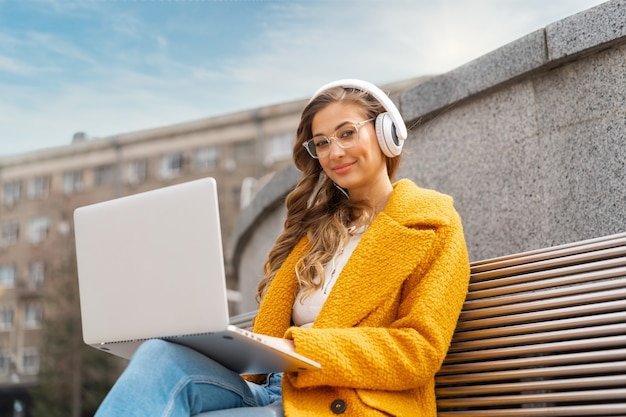 Mulher de negócios usa óculos ouvir música fone de ouvido ao ar livre banco de assento usando laptop ao ar livre vestido elegante casaco amarelo sorriso mulher branca 30 anos desfrutar de podcast ou audiolivros lá fora