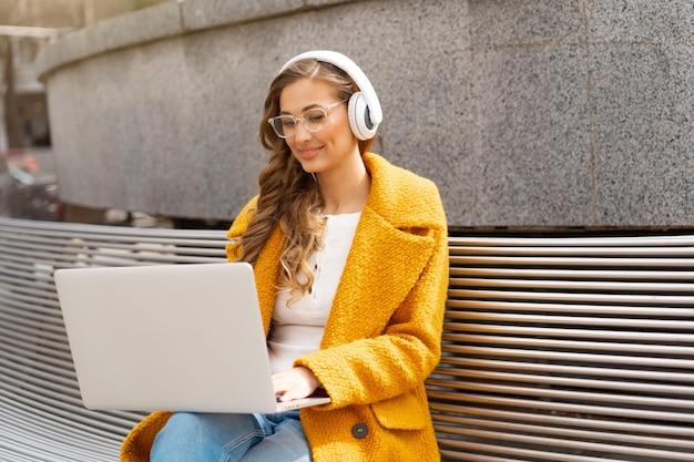 Mulher de negócios usa óculos ouvir música fone de ouvido ao ar livre banco para sentar usando laptop ao ar livre vestido elegante casaco amarelo sorriso mulher branca 30 anos desfrutar de podcast ou audiolivros lá fora