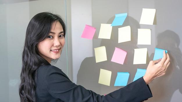 Mulher de negócios usa papel post stick no vidro e em pé na frente da guerra de vidro no quarto.