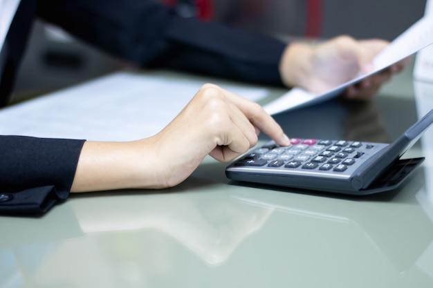 Mulher de negócios usando a calculadora. conceito econômico, tecnologia e finanças