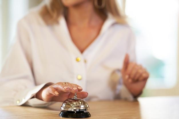 Mulher de negócios usando a campainha na recepção do hotel