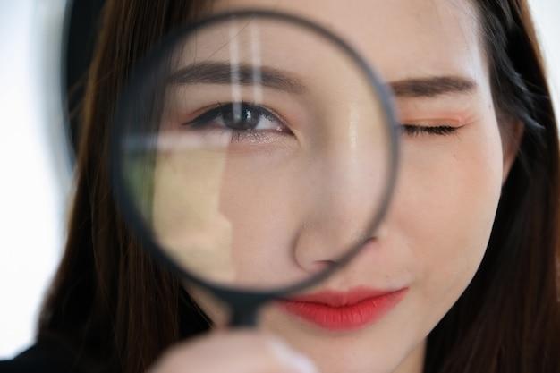 Mulher de negócios usando ampliação para usar o conceito de auditoria ou verificação.