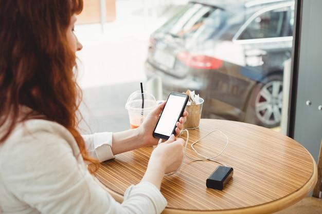 Mulher de negócios usando banco de energia portátil para carregar o telefone