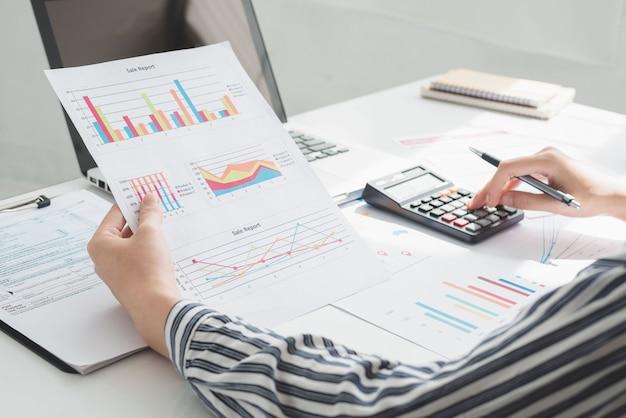 Mulher de negócios usando calculadora e escrevendo anote com calcular. impostos e conceitos econômicos.