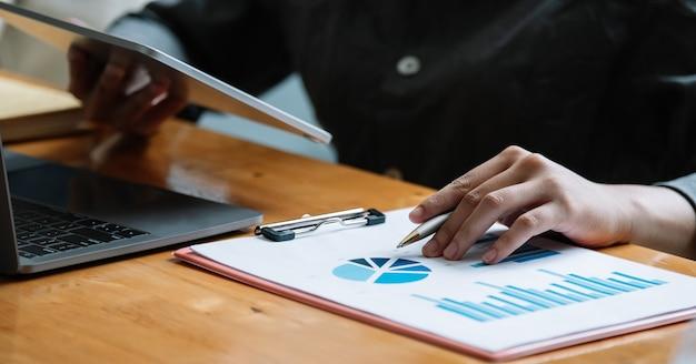 Mulher de negócios usando computador tablet para relatório financeiro de análise