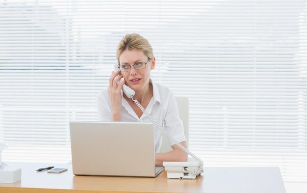 Mulher de negócios usando laptop e telefone na mesa