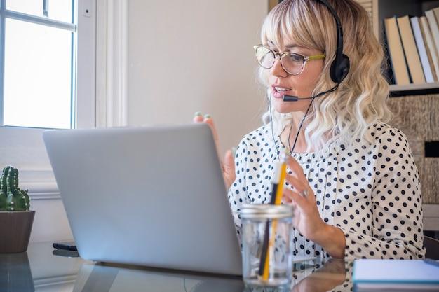 Mulher de negócios usando laptop enquanto fala em fones de ouvido com microfone em casa mulher jovem confiante