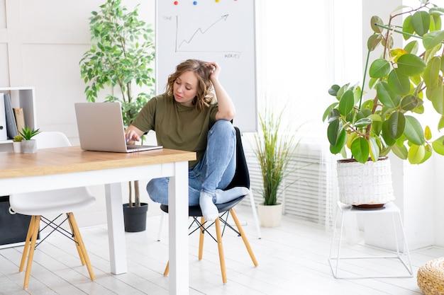 Mulher de negócios usando laptop sentado mesa escritório branco interior com planta de casa procurando pessoas de negócios pessoa de negócios online, jovem e bem-sucedido dresed camisa verde jeans descalço relaxante