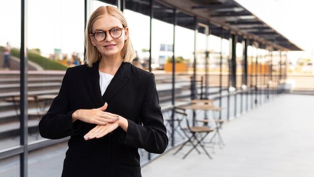 Mulher de negócios usando linguagem de sinais ao ar livre no trabalho