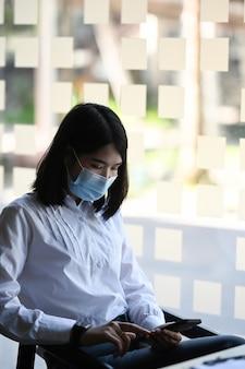 Mulher de negócios, usando máscara protetora, fazendo uma pausa em seu espaço de trabalho e usando telefone celular.