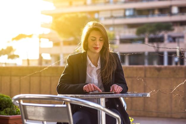 Mulher de negócios usando o tablet na mesa do lado de fora